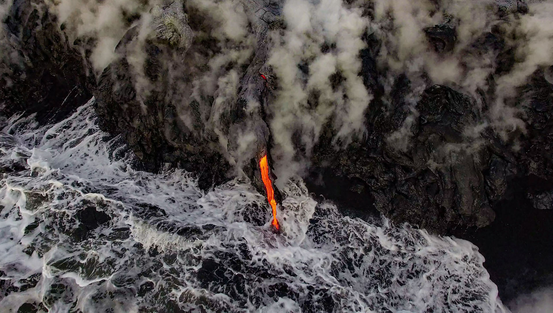 Molten Earth meets the ocean on the flanks of Kilauea volcano on the Big Island of Hawai'i.  A perspective not seen until the advent of drones, this interaction between lava, water, and time contributes to the buildup of an island chain.