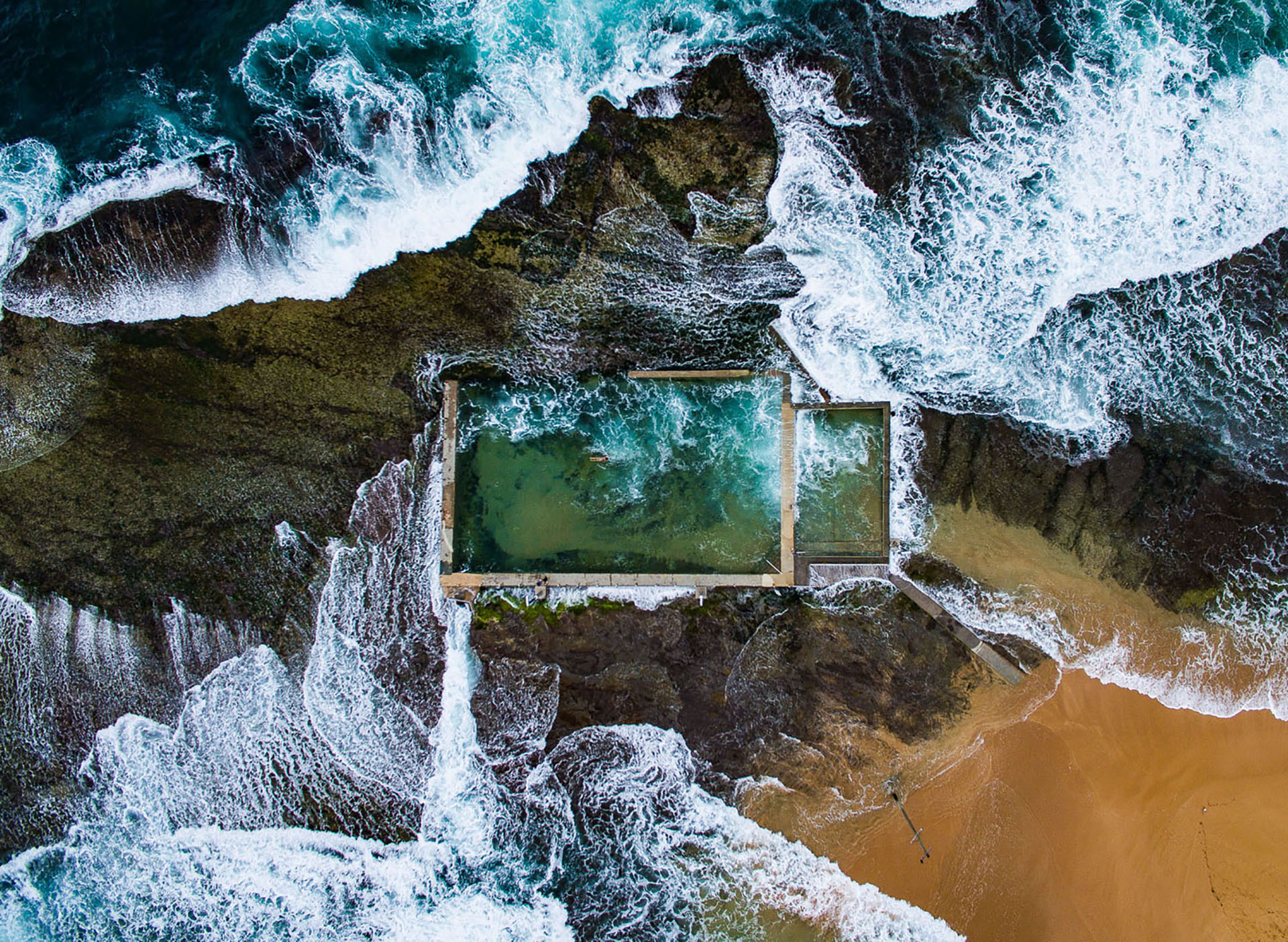 A rock pool in sydney, Australia at high tide. Waves crash over the edge. a long swimmer is undeterred.