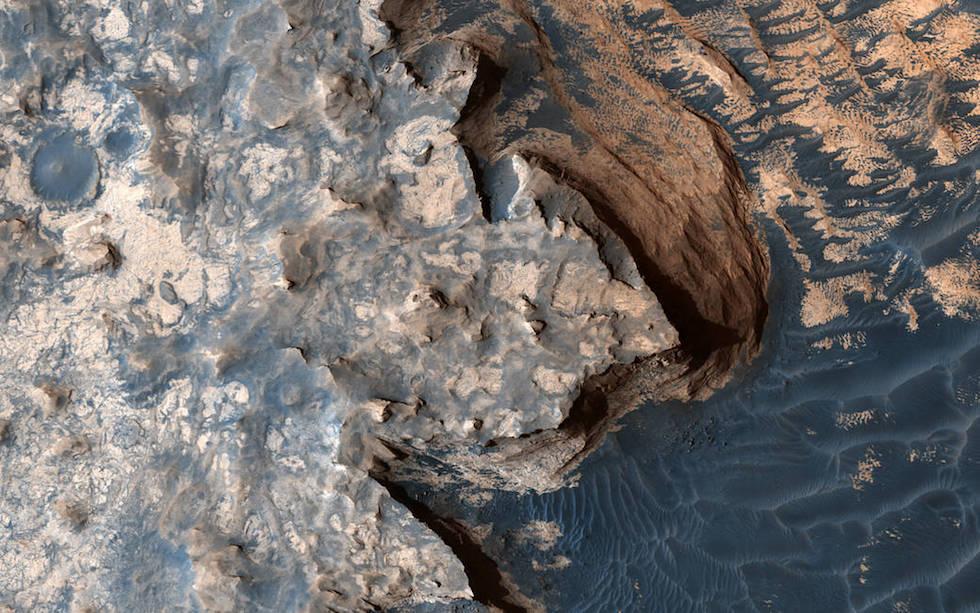 Una fotografia aerea del Meridiani Planum, una grande pianura in prossimità dell'equatore di Marte, nel settore più occidentale del Meridiani Sinus. Quello visibile a destra e che ricorda un oceano ondoso è in realtà un'ampia area desertica, che termina in una zona molto scoscesa e con ripide pareti rocciose, simili a una scogliera terrestre. L'immagine è stata realizzata dalla sonda spaziale Mars Reconnaissance Orbiter, in orbita intorno al pianeta.   (NASA/JPL/University of Arizona)