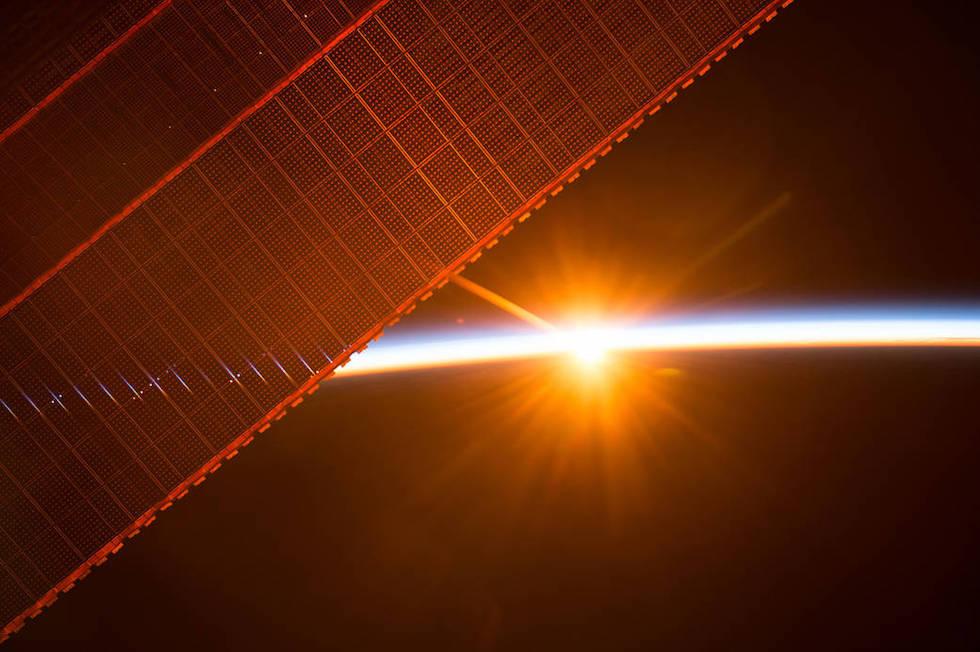 I pannelli solari della Stazione Spaziale Internazionale durante una delle 16 albe cui assistono ogni giorno gli astronauti che vivono a bordo.  (ESA/NASA)