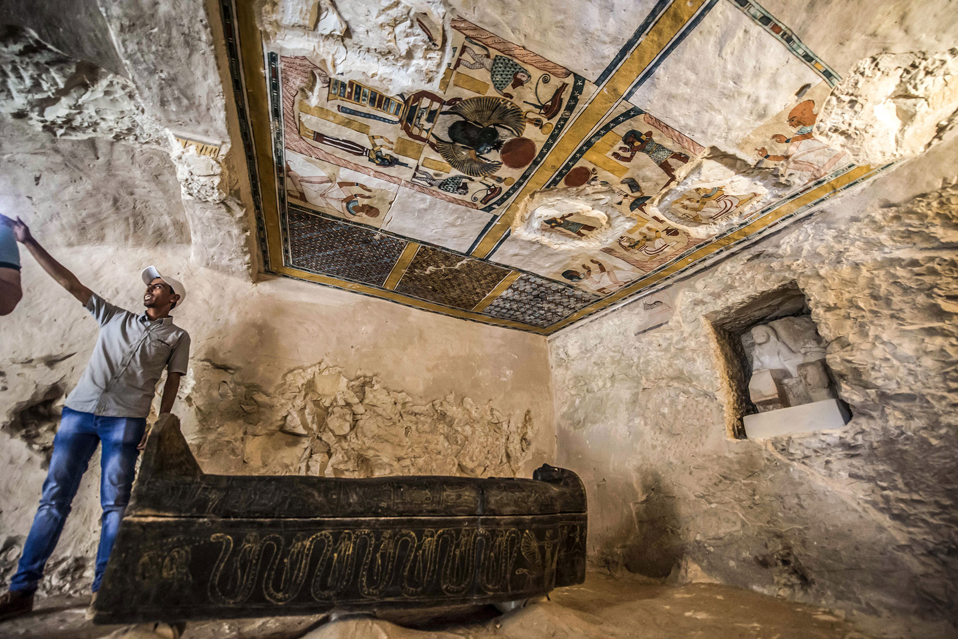 This picture taken on November 24, 2018 shows a carved black wooden sarcophagus inlaid with gilded sheets, dating to Egypt's Late period (7th-4th century BC), lying in a burial chamber decorated with colored scenes depicting the owner with members of his family, discovered by an Egyptian archaelogical mission at the site of Tomb TT28 at Al-Assasif  necropolis on the west bank of the Nile north of the southern Egyptian city of Luxor. - Located between the royal tombs at the Valley of the Queens and the Valley of the Kings, the Al-Assasif necropolis is the burial site of nobles and senior officials close to the pharaohs. (Photo by Khaled DESOUKI / AFP)