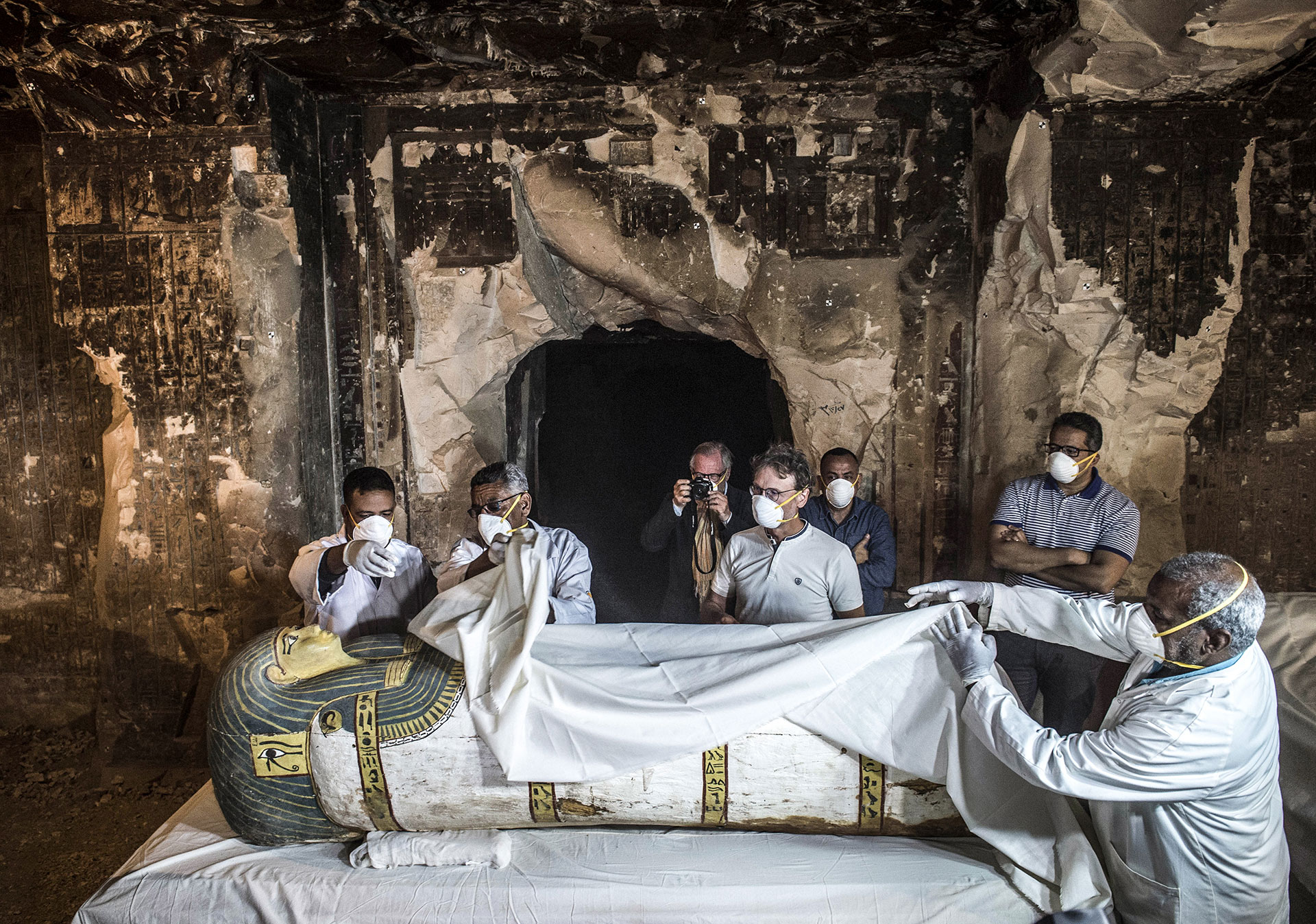 Egypt's Antiquities Minister Khaled el-Enany (R) and Mostafa Waziri (2nd-R, behind), the Secretary General of the Supreme Council of Antiquities, inspect an intact sarcophagus during its opening at the site of Tomb TT33 at Al-Assasif necropolis on the west bank of the Nile north of the southern Egyptian city of Luxor on November 24, 2018, after it was discovered earlier this month by a French mission. - Located between the royal tombs at the Valley of the Queens and the Valley of the Kings, the Al-Assasif necropolis is the burial site of nobles and senior officials close to the pharaohs. (Photo by Khaled DESOUKI / AFP)